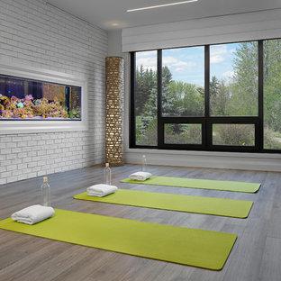 Imagen de estudio de yoga actual, de tamaño medio, con paredes grises y suelo de madera clara