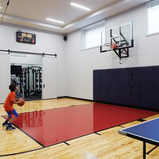 Example of a trendy light wood floor and beige floor indoor sport court design in Chicago with white walls