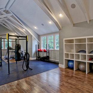 Esempio di una grande sala pesi country con pareti grigie, pavimento in legno massello medio e pavimento marrone