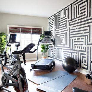 Esempio di una palestra in casa minimalista di medie dimensioni con pareti grigie, pavimento in laminato e pavimento marrone