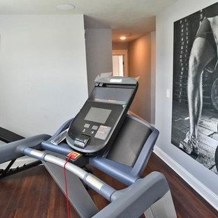 Idee per una sala pesi american style di medie dimensioni con pareti grigie, pavimento in laminato e pavimento marrone