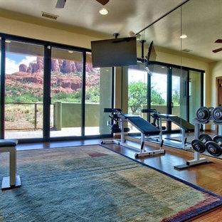 Foto di una sala pesi american style di medie dimensioni con pareti beige e pavimento in legno massello medio