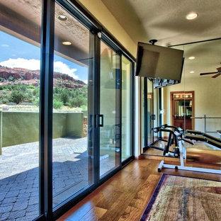 Esempio di una sala pesi stile americano di medie dimensioni con pareti beige e pavimento in legno massello medio