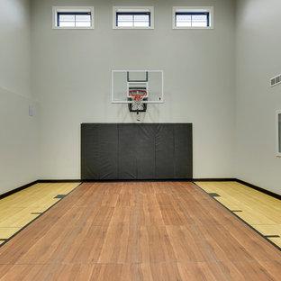 Esempio di un grande campo sportivo coperto country con pareti grigie, pavimento marrone e pavimento in legno massello medio