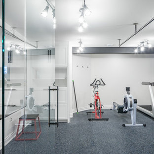 This is an example of a large industrial multi-use home gym in Ottawa with white walls.