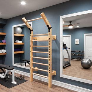 Imagen de sala de pesas tradicional renovada, grande, con paredes azules, suelo de madera clara y suelo beige
