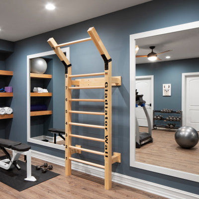 Large transitional light wood floor and beige floor home weight room photo in Milwaukee with blue walls