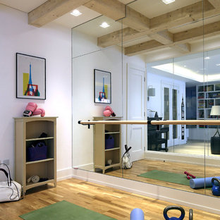 This is an example of a contemporary home gym in London with white walls, medium hardwood flooring and brown floors.