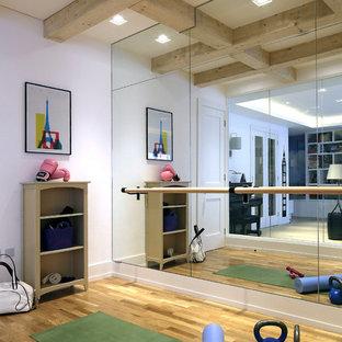 Foto di una palestra in casa design con pareti bianche, pavimento in legno massello medio e pavimento marrone