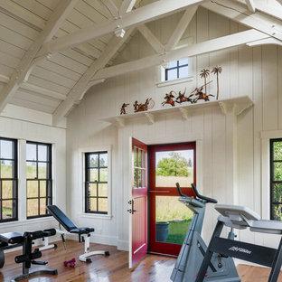 Esempio di una palestra in casa country con pareti bianche e pavimento in legno massello medio