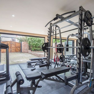 This is an example of a medium sized contemporary home weight room in Other with beige walls, dark hardwood flooring and black floors.