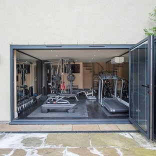 Medium sized contemporary multi-use home gym in Other with beige walls, dark hardwood flooring and black floors.
