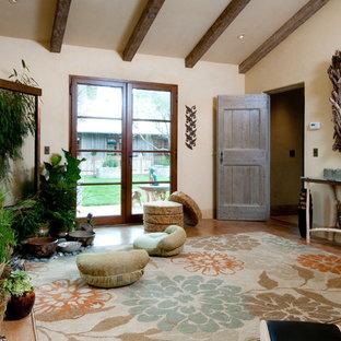 Idee per uno studio yoga boho chic con pareti beige e pavimento in legno massello medio