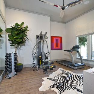 Esempio di una sala pesi boho chic di medie dimensioni con pareti grigie, pavimento in legno massello medio e pavimento marrone