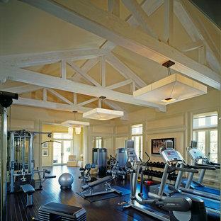 Klassischer Fitnessraum mit gelber Wandfarbe, dunklem Holzboden und schwarzem Boden in Los Angeles