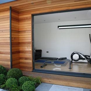 Immagine di una grande palestra in casa minimal con pareti bianche e parquet chiaro