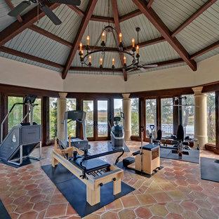 Multifunktionaler, Großer Mediterraner Fitnessraum mit beiger Wandfarbe, Terrakottaboden und rotem Boden in Atlanta