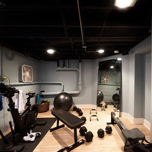 Photo of a small arts and crafts multipurpose gym in Chicago with grey walls, vinyl floors and brown floor.