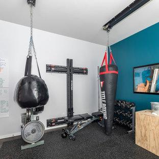 Idee per una sala pesi moderna di medie dimensioni con pareti blu, pavimento in sughero e pavimento nero
