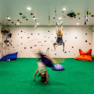 Immagine di una grande parete da arrampicata contemporanea con pareti bianche e moquette