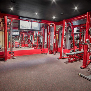 Exemple d'une grande salle de musculation moderne avec un mur rouge et un sol gris.