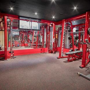 Großer Moderner Kraftraum mit roter Wandfarbe und grauem Boden in Calgary