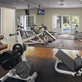 Ispirazione per una grande sala pesi tradizionale con pareti beige e pavimento in legno massello medio