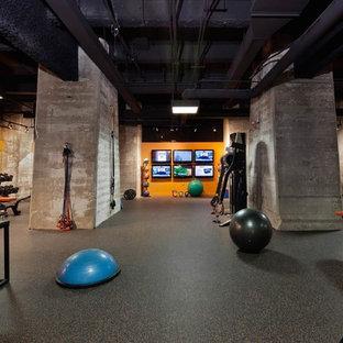Cette photo montre une grand salle de sport industrielle multi-usage avec un mur orange, un sol en liège et un sol noir.