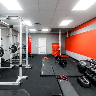 Modelo de sala de pesas minimalista, grande, con paredes grises y suelo negro
