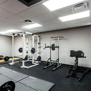 Idee per una grande sala pesi minimalista con pareti grigie e pavimento nero