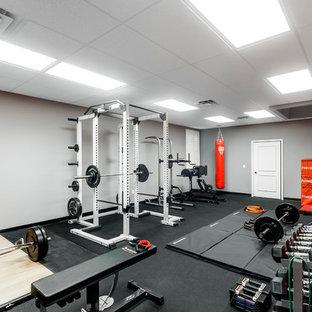 Foto di una grande sala pesi moderna con pareti grigie e pavimento nero