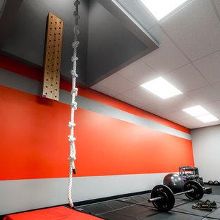 Großer Moderner Fitnessraum mit Kletterwand, roter Wandfarbe und grauem Boden in Orlando
