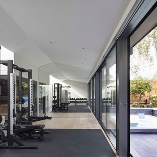 Photo of a medium sized contemporary multi-use home gym in London with white walls, light hardwood flooring and beige floors.