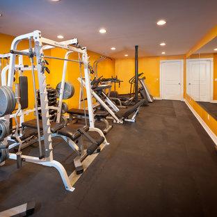ニューヨークの広いコンテンポラリースタイルのおしゃれなトレーニングルーム (黄色い壁、黒い床) の写真