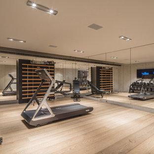 Multifunktionaler, Großer Moderner Fitnessraum mit hellem Holzboden und grauer Wandfarbe in London