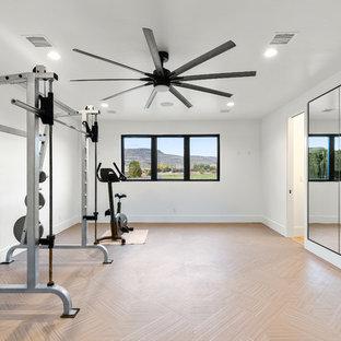 Ispirazione per un'ampia palestra multiuso design con pareti bianche, parquet chiaro e pavimento beige
