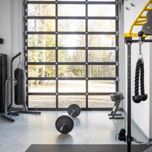 Moderner Fitnessraum mit weißer Wandfarbe, Betonboden und grauem Boden in Edmonton