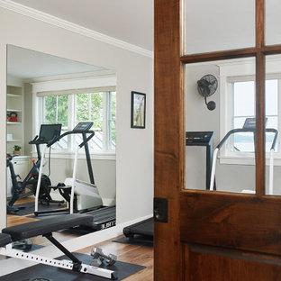 Esempio di una piccola sala pesi costiera con pareti grigie, pavimento in legno massello medio e pavimento marrone