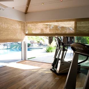 Esempio di una sala pesi tradizionale di medie dimensioni con pareti bianche e pavimento in legno massello medio