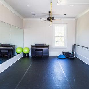 Multifunktionaler, Großer Klassischer Fitnessraum mit beiger Wandfarbe, gebeiztem Holzboden und schwarzem Boden in Sonstige