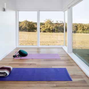 Mittelgroßer Moderner Yogaraum mit weißer Wandfarbe, hellem Holzboden und beigem Boden in Austin