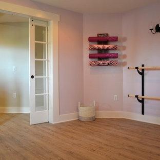Ispirazione per uno studio yoga country di medie dimensioni con pareti viola e pavimento in legno massello medio