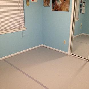 Immagine di uno studio yoga minimalista di medie dimensioni con pareti blu, pavimento in vinile e pavimento grigio