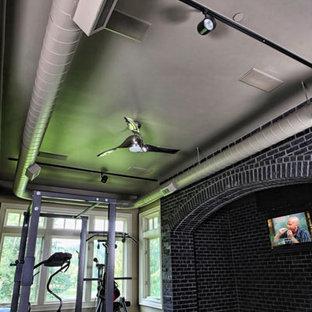 Inredning av ett industriellt mellanstort hemmagym med grovkök, med svarta väggar och mörkt trägolv