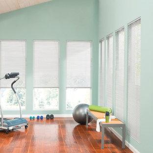 Immagine di una palestra in casa minimal con pavimento in legno massello medio