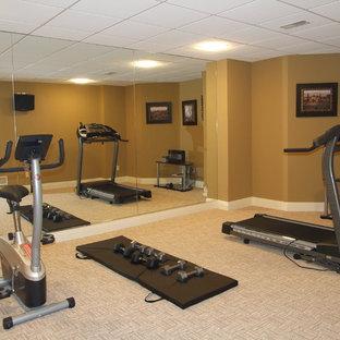 Immagine di una sala pesi stile americano di medie dimensioni con pareti marroni e moquette