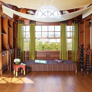 Mittelgroßer Yogaraum mit beiger Wandfarbe, dunklem Holzboden, braunem Boden und gewölbter Decke in New York