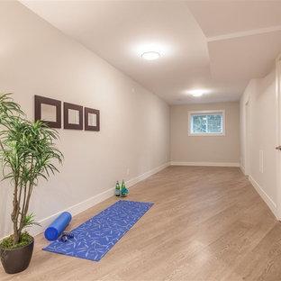 Foto di un piccolo studio yoga minimalista con pareti grigie e pavimento in legno massello medio