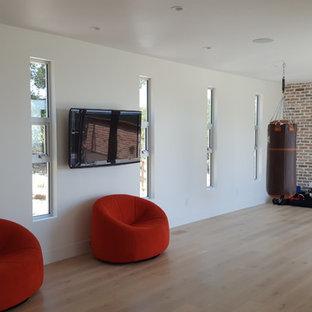 Immagine di una grande palestra multiuso moderna con pareti bianche, parquet chiaro e pavimento beige