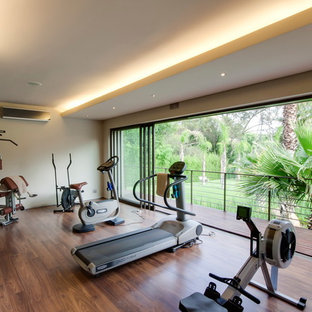 Inspiration for a large contemporary multi-use home gym in Other with beige walls and brown floors.